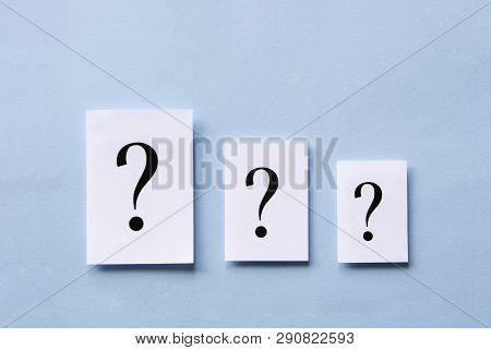 Three White Cards With Printed Question Marks Arranged In Descending Size On A Blue Background In A