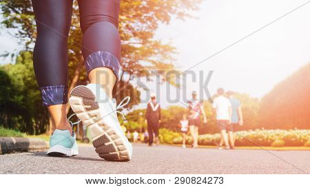 Young Fitness Woman Legs Walking With Group Of People Exercise Walking In The City Public Park In Mo