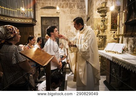 Priest Of The Church Of Holy Sepulchre Gives Holy Communion To Faithful Man With Other Believers Wai