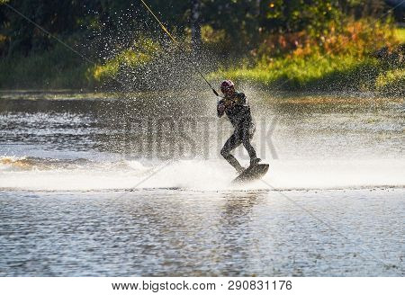 Wakeboarder Surfing Across A Lake With Water Splashing. This Is An Extreme Sport.