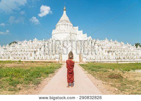 Burmese Monk Standing In Front Of Hsinbyume Or Myatheindan Pagoda In Sagaing Region Of Myanmar.
