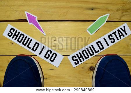 Should I Go Or Should I Stay Opposite Direction Signs With Sneakers On Wooden Vintage Background. Bu