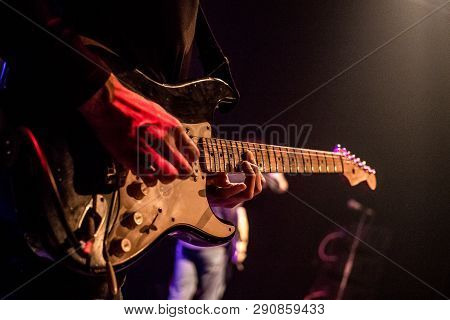 The Guitarist Plays An Electric Guitar On Stage With Lights In The Background. Close Up