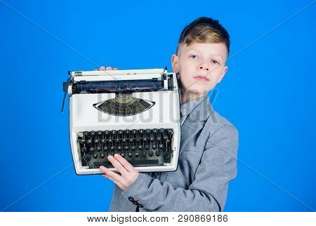 Using Retro Technology. Little Boy Holding Retro Typewriter On Blue Background. Small Boy Having Old