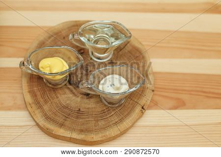 Set Of Three Transparent Sauceboats With Different Sauces On Wooden Plate.