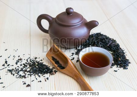 Dishes For Tea And Black Tea Sprinkled On The Table . Tea Ceremony Set And Black Flavored Tea On Woo