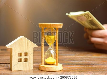 Wooden House And Clock. Businessman Counting Money. Payment Of Deposit Or Advance Payment For Rentin