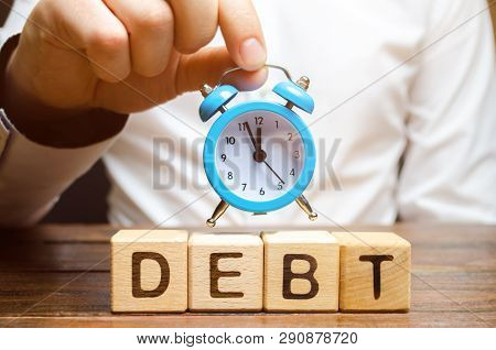Wooden Blocks With The Word Debt And The Clock In The Hands Of A Businessman. Timely Payment Of Debt