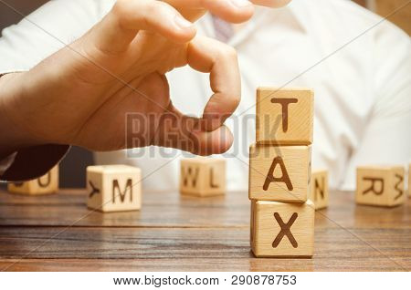 Businessman Removes Wooden Blocks With The Word Tax. The Concept Of Reducing The Tax Burden. Tax Avo