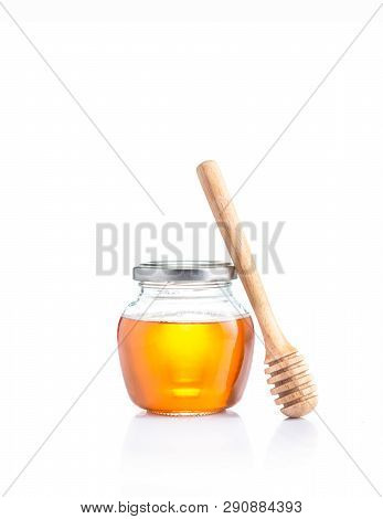 Honey In Closed Lid Glass Jar And Wodden Honey Dipper Leaning On The Jar, All On White Background Wi