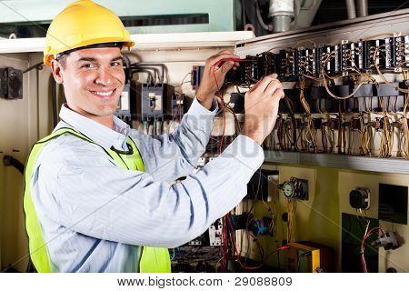 glücklich männlich Elektriker arbeiten auf industrielle Maschine