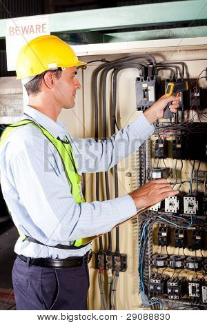 industrial technician checking machine control box temperature