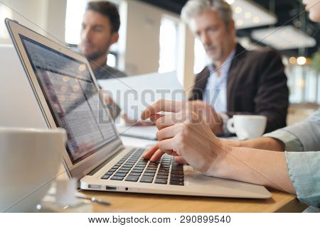 Close up of business woman's hands typing during meeting