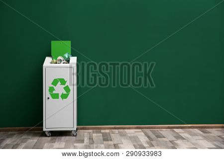 Overfilled Trash Bin With Recycling Symbol Near Color Wall Indoors. Space For Text