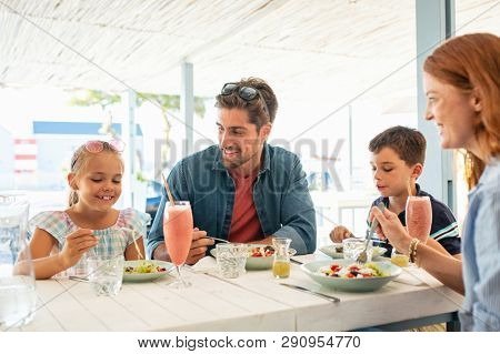 Cheerful family in restaurant enjoying lunch together in a patio. Smiling mother and father with two children eating brunch together at kiosk during summer vacation.