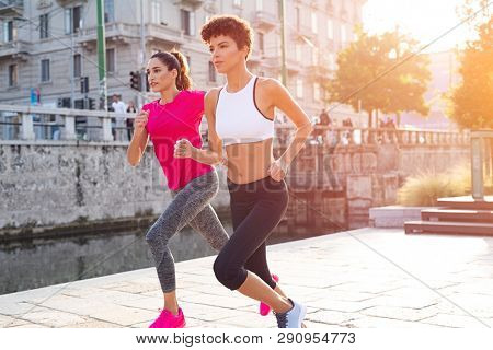 Fitness friends exercising together on the street. Two multiethnic women joggers pursuing their activity outdoors in the city. Young women running in city park at sunset.