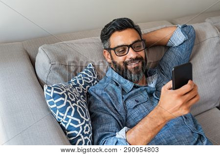 Happy smiling latin man using smartphone device while sitting on sofa at home. Mature indian man lying on couch reading messages on mobile phone. Hispanic guy with eyeglasses relaxing at home.