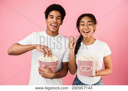 African-american Teen Couple Eating Popcorn, Watching Movie On Pink Background