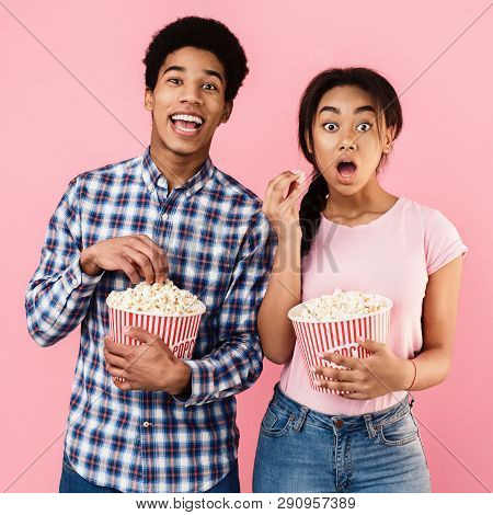 Shocked Teen Couple Eating Popcorn Over Pink Background