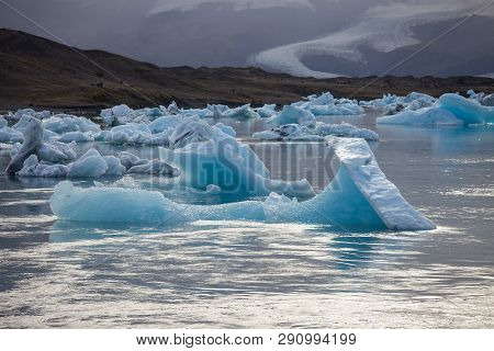 Amazing Transparent Blue Iceberg Pieces In Jokulsarlon Lagoon, Iceland. Ice Calving.
