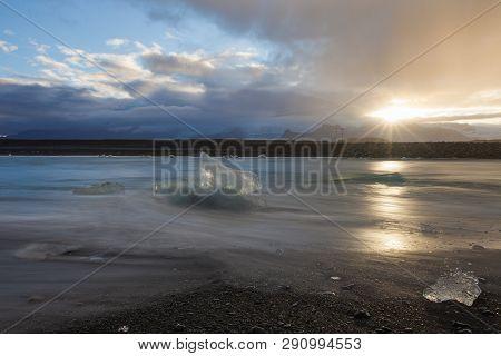 Dramatic A Sunset With Amazing Transparent Blue Iceberg Pieces On Diamond Beach With Black Sand Near