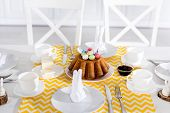 Easter cake with painted eggs and crockery on table poster