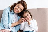Blissful mother and daughter sitting on brown sofa and talking on smartphone isolated on white poster
