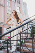 Pretty young lady posing on the street near the handrail standing on the steps dressed in a long dress poster