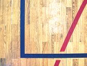 Hall floor in a gymnasium with diverse lines. Worn out wooden floor of sports hall with colorful marking lines. Schooll gym hall poster