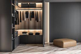 Modern Wooden Wardrobe With Clothes Hanging On Rail In Walk In Closet Design Interior. 3D Render