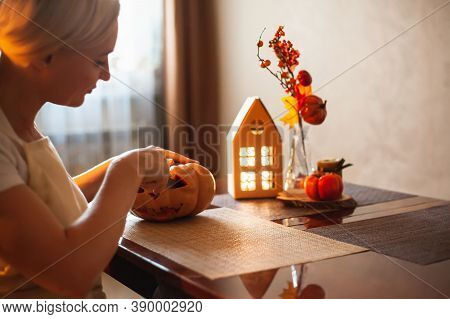 A Woman Carves A Pumpkin For Halloween In A Room With Autumn Decor And A Lamp House. Cosy Home And P
