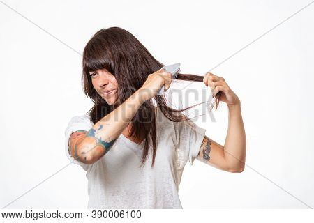 A Woman With Tattoos Combs A Lock Of Hair, Experiencing Pain And Pulling Out Her Hair. White Backgro