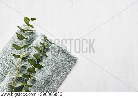 Rolled Fluffy Towel And Green Eucalyptus Branch On White Background. Minimalist Scandinavian Style.