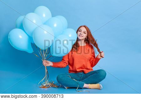 Young Happy Girl With Bunch Of Helium Balloons Sitting On Floor With Crossed Legs, Touches Her Hair,