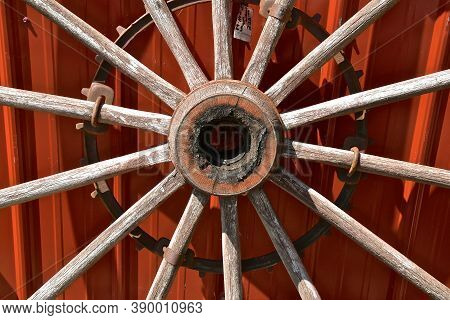 The Hub Of An Old Wooden Wheel With The Extending Spokes Against A Red Wall.