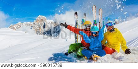 Skiing family enjoying winter vacation on snow in sunny cold day in mountains and fun. San Martino di Castrozza, Italy.