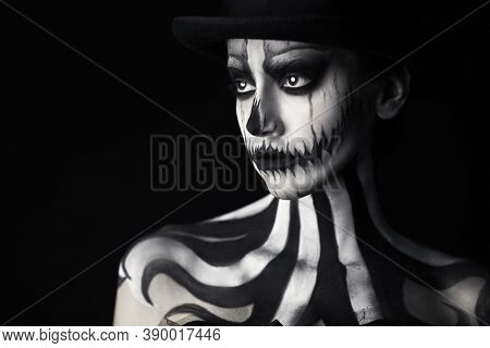 Elegant young woman in a male top-hat with pumpkin skull make-up over black background. Pumpkin queen. Costumes and makeup for Halloween. Copy space.