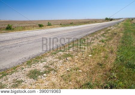 Roadside Of An Empty Rural Highway Is Under Blue Sky At Summer Day. Landscape Photo With European Ro