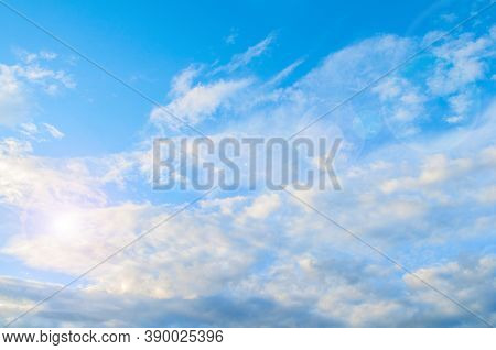 Blue sky background. White dramatic fluffy clouds lit by sunset light. Vast sky scene, blue sky view. Dramatic blue sky background, vast sky landscape. Colorful blue sky view in bright tones. Sky landscape, vast sky scene