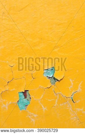 Texture background of bright yellow peeling paint with blue streaks on the old concrete surface.Texture background of peeling paint, yellow peeling paint on the texture surface, peeling paint texture on the texture background. Texture surface