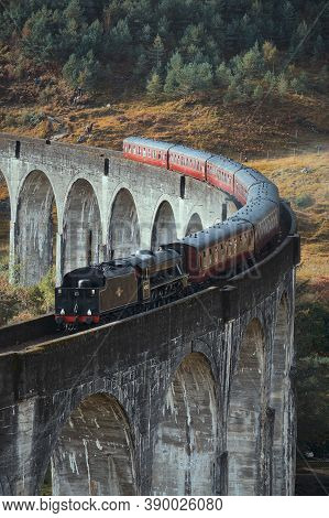Old Historical Steam Train Riding On Famous Viaduct Bridge. Travel And Tourist Destination In Europe