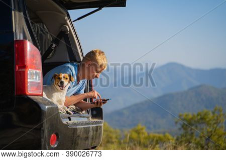 A young man is resting in nature with an off-road vehicle and a jack russell terrier dog. Uses a cell phone for mobile communication and the Internet.