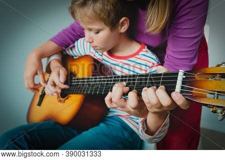 Mother Teaching Kid To Play Guitar At Home