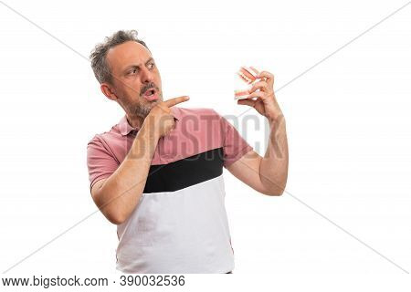 Surprised Adult Male Wearing Colourful Summer Attire Pointing Index Finger At Fake Teeth Denture Wit