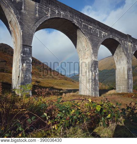 Bottom View Of The Old Arched Bridge Or Viaduct Against The Background Of The Sky With A Rainbow. Bl