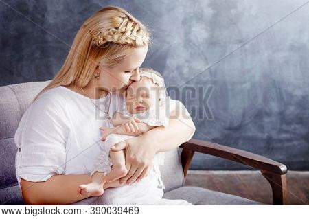 Pretty Woman Holding A Newborn Baby Girl In Her Arms. Happy Mother And Her Slipping Newborn Baby.  H
