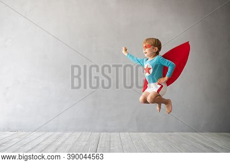 Superhero Child Jumping Against Grey Concrete Background. Super Hero Kid Playing At Home. Childhood