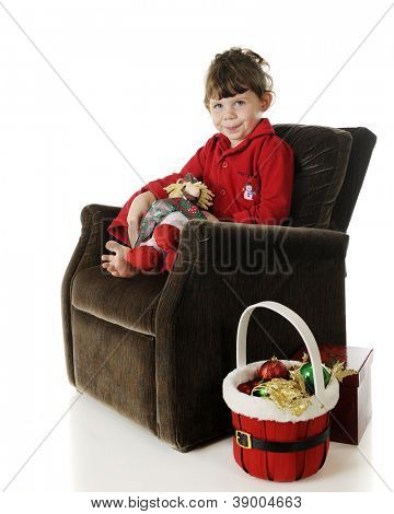 An adorable preschooler in her pajamas, happily sitting in her overstuffed chair by a basket of Christmas ornaments.  On a white background.