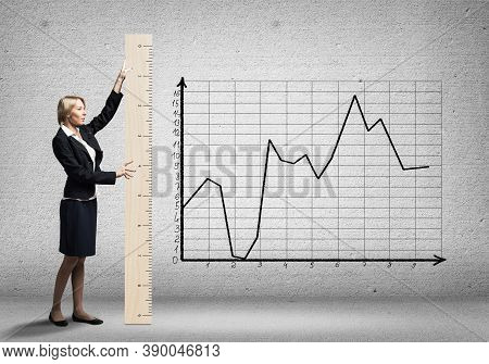 Woman Holding Big Ruler On Wall Background. Business Development To Success. Businesswoman Measuring