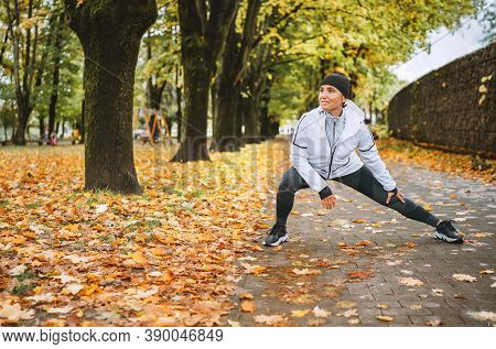 Young Fit Athletic Woman Wears Modern Running Clothes Standing On The Footway Before Jogging In The